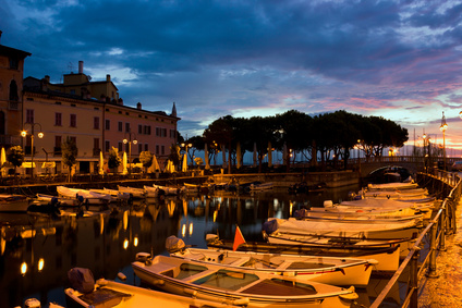 Desenzano Del Garda marina with fishing boats in early morning, just before dawn.